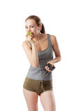 Slim woman in fitness dress is eating an apple and listening music. Isolated on white Stock Images