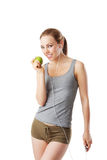Slim woman after fitness workout going to eat an green apple. Isolated on white Royalty Free Stock Photography