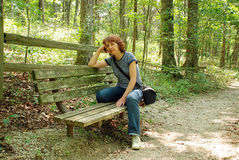 Slim woman has a rest. Sitting on a bench in the park Stock Images