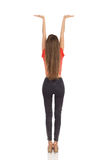 Slim Woman Holding Something Above Her Head. Rear View. Stock Photos