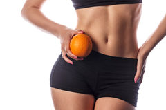 Slim woman holds an orange. Royalty Free Stock Photography