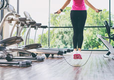 Slim woman jumping with skipping rope. Fitness concept. Healthy lifestyle. Young slim woman jumping with skipping rope in gym Stock Photos