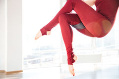 Slim woman legs doing aerial yoga exercise in studio Stock Images