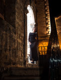 Slim woman in long dress leaning against old stone arch at night Stock Images
