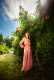 Slim woman in long dress posing at flowering bushes at park Royalty Free Stock Photo