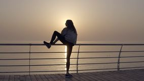 Slim woman with long legs doing stretching on sunrise by the seaside, perfect body. Stretches her leg above head. Backside view stock footage
