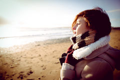 Slim woman looking at the sea during the sunset Royalty Free Stock Images
