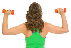 Slim woman making exercise with dumbbells . rear view Stock Images