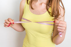 Slim woman measures her breast with a measuring tape Royalty Free Stock Photos