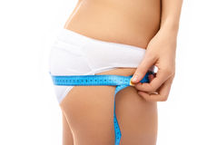 Slim woman measures her hips Royalty Free Stock Photography