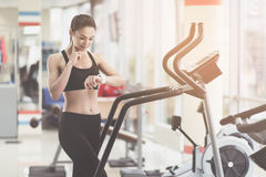 Slim woman measuring her pulse rate in a gym Royalty Free Stock Images