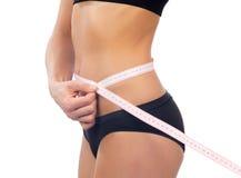 Slim woman measuring her waist metric tape measure stock photos