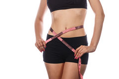Slim woman measuring waist after diet. Royalty Free Stock Images