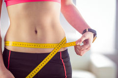 Slim woman measuring waist with tape measure Royalty Free Stock Photo