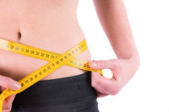Slim woman measuring waist with tape measure Royalty Free Stock Images