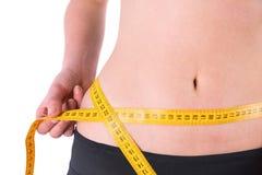 Slim woman measuring waist with tape measure Royalty Free Stock Photo