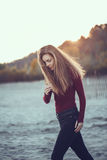 Slim woman with messy long hair wearing black jeans and red shirt walking on windy autumn day outdoor on beach. Portrait of young Caucasian slim woman with messy Stock Photography