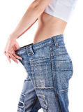 Slim woman in oversized pair of blue jeans Stock Photos