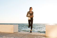 Slim woman with perfect body running at the seaside. In the morning Stock Photos