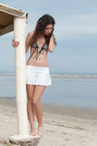 Slim woman pose by the sea wearing mini skirt and bra Stock Photo