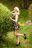 Slim woman posing at garden against bush Royalty Free Stock Photography