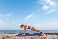 Slim woman practicing plank pose royalty free stock image