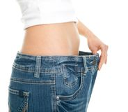 Slim woman pulling oversized jeans Stock Photos