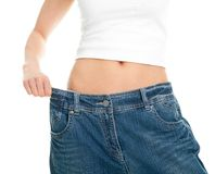 Slim woman pulling oversized jeans Stock Photo