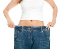 Slim woman pulling oversized jeans royalty free stock photos