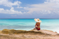 Slim woman in red swimsuit, sits at rocky beach Stock Image