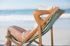 Slim woman relaxing in deck chair on the beach Stock Photos