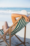 Slim woman relaxing in deck chair on the beach Stock Photography