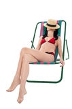 Slim woman relaxing. Face covered with hat. Royalty Free Stock Image
