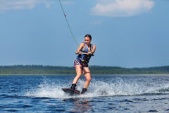 Slim woman riding wakeboard on wave of boat Royalty Free Stock Image