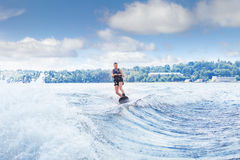 Slim woman riding wakeboard on wave of boat. Young pretty slim brunette woman riding wakeboard on wave of motorboat in a summer lake Royalty Free Stock Images