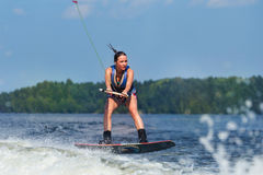 Slim woman riding wakeboard on wave of boat Royalty Free Stock Photos