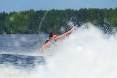 Slim woman riding wakeboard on wave of boat Royalty Free Stock Images