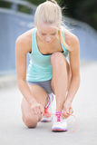 Slim woman runner tying shoelaces on bridge Stock Photos