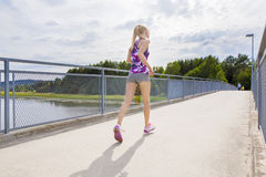 Slim woman running outdoor on bridge over a lake Stock Photo
