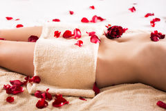 Slim woman's body. Beautiful female body covered with a towel and petals of roses Stock Photography