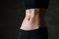 Slim woman's body over dark grey background Stock Image
