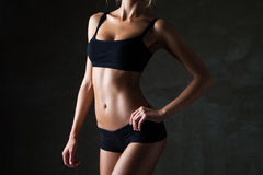 Slim woman's body  over dark grey background Royalty Free Stock Images