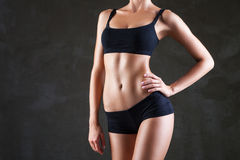 Slim woman's body  over dark grey background Royalty Free Stock Photos