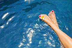 Woman`s legs on surface of blue pool water