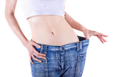Slim woman shows her weight loss by wearing an old jeans Stock Images