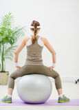 Slim woman sitting on fitness ball back to camera Stock Photos