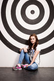 Slim woman sitting on floor against wall with big painted target Royalty Free Stock Photos