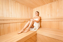 Slim woman sitting in wooden steam bath Stock Images
