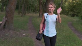 Mature Woman Goes On After Exercising in the Wood, Waves Us by Hand Sending an Air Kiss Holding on the Shoulder Yoga Mat stock video