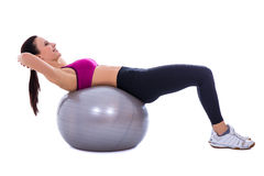 Slim woman in sports wear doing exercises on fitness ball isolat Stock Image